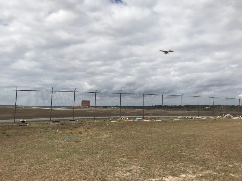 Plane crossing over Airport Cemetery to land on runway 27